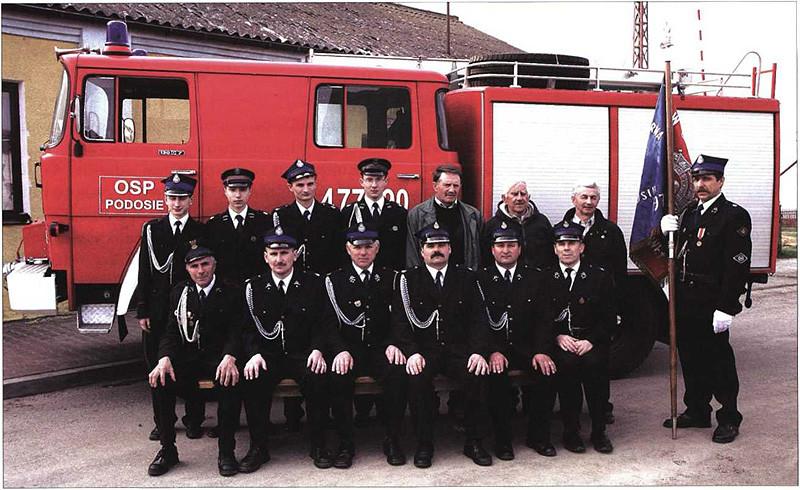Na zdjęciu jednostka straży pożarnej w  Podosiu na tle wozu strażackiego